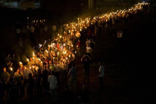 White supremacists march through the University of Virginia on Friday. Clashes with counterprotesters...
