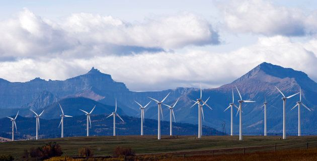 Windmills generate electricity in the windy rolling foothills of the Rocky Mountains near the town of...