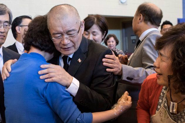 Canadian pastor Hyeon Soo Lim is embraced by a member of the congregation following a service at the...