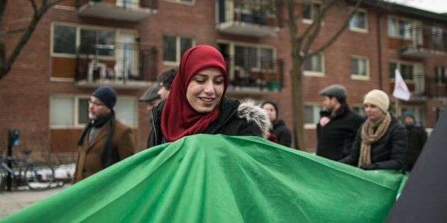 People carry a massive flag during a march against racism and Islamophobia in Montreal, Que., on March...