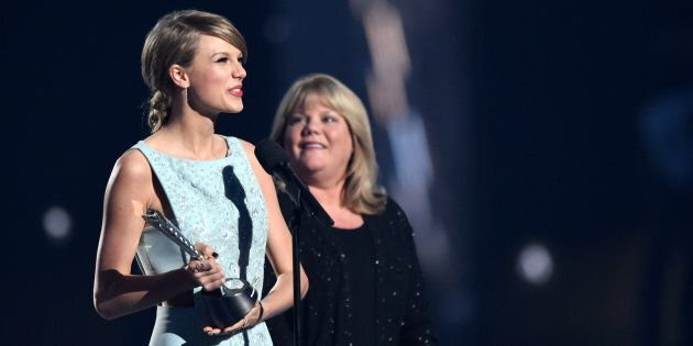 Honoree Taylor Swift (L) accepts the Milestone Award from Andrea Swift onstage during the 50th Academy...