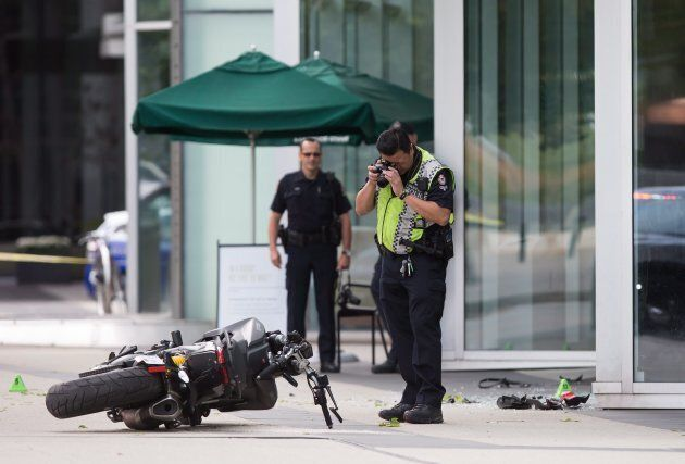 A police officer photographs a motorcycle after a stunt driver working on the movie