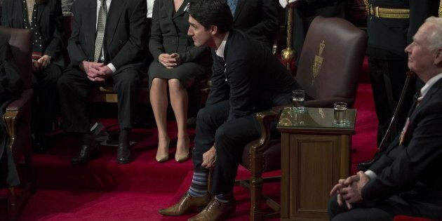 Canada's Prime Minister Justin Trudeau pulls up his socks before the start of the Speech from the Throne in the Senate chamber on Parliament Hill in Ottawa, Canada December 4, 2015. (REUTERS/Fred Chartrand/Pool)