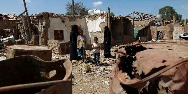Yemeni family members stand outside their house which was damaged several months ago in an air strike...