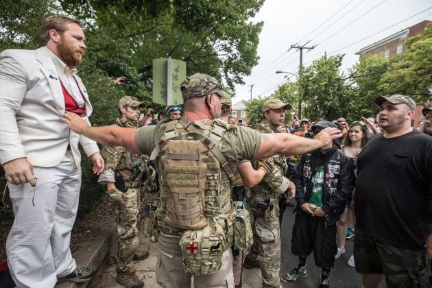 White supremacist groups and counter protestors argue while a member of