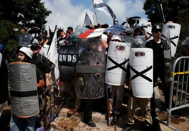 White supremacists shelter behind their shields after clashing with counter protesters at a rally in...