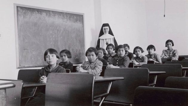 A group of female students and a nun pose in a classroom at Cross Lake Indian Residential School in Cross...