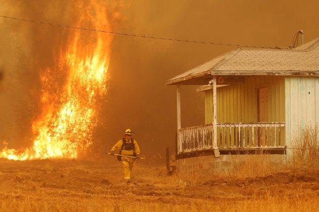 A firefighter walks near a home as flames from the fast-moving Detwiler fire approach in Mariposa, California,...