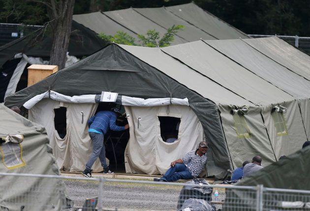 A group of asylum seekers wait in their tent encampment in Lacolle, Que., Aug. 11,