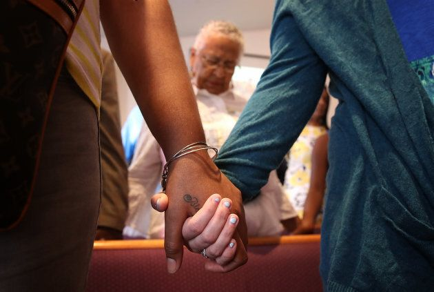 Worshipers hold hands during morning services at Mount Zion First African Baptist Church Aug. 13, 2017...