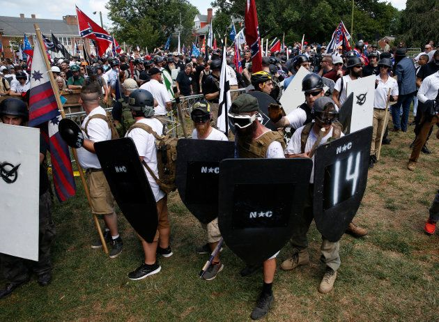 Members of white nationalist protesters hold shields as they clash against a group of counter-protesters...