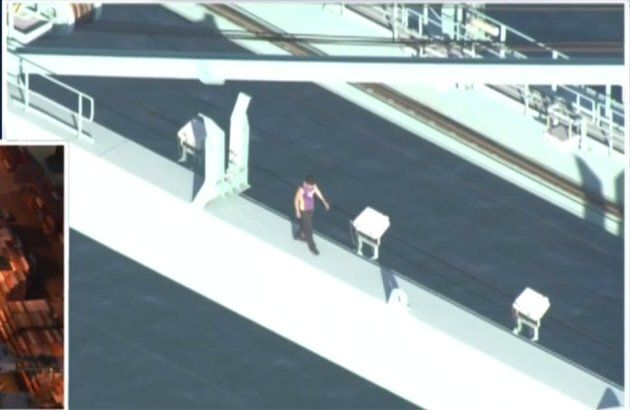 The man climbed up the crane and stripped his clothes