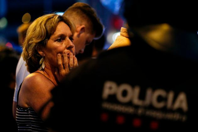 A woman is escorted by Spanish policemen outside a cordoned off area after a van ploughed into a crowd of people in Barcelona on Thursday.