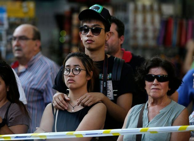 People stands behind police tape on a street in Barcelona on Thursday.