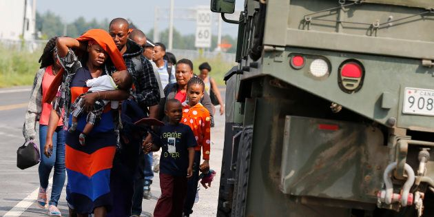 A group of asylum seekers pass a Canadian army vehicle as they walk down the street while escorted from...