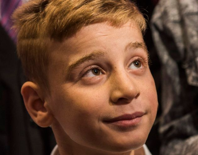 12-year-old son Emad Mishko Tamo looks on as he's reunited with friends and family at Winnipeg's James...