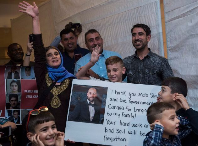 Mother Nofa Mihlo Rafo, left, and uncle Hadji Tamo, right, stand with 12-year-old Emad Mishko Tamo as...