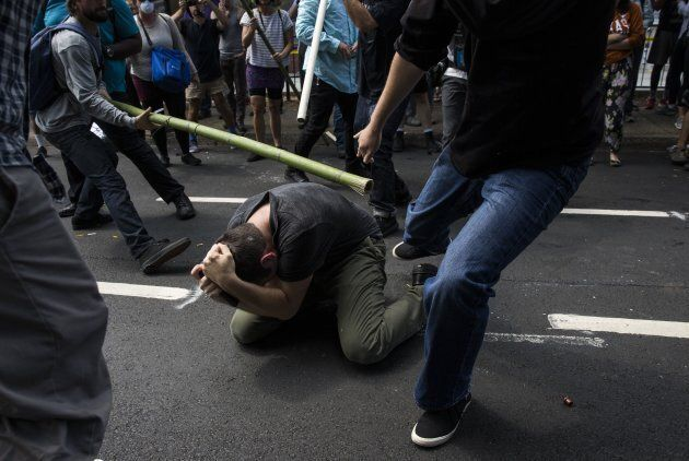 Counter protestors beat a white nationalist during clashes at Emancipation Park where the White Nationalists...