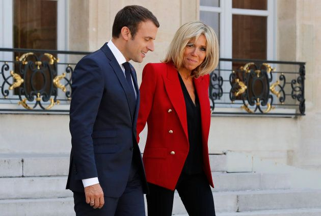 French President Emmanuel Macron (L) and wife wife Brigitte Macron (R) leave the Elysee Palace on July...