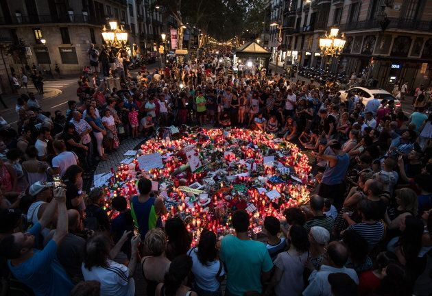 People gather around tributes laid on Las Ramblas near to the scene of yesterday's terrorist attack,...