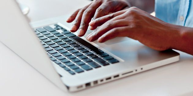 Close-up on male hands typing on laptop
