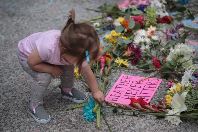 A young girl puts flowers on a memorial to Heather Heyer that was chalked on the pavement during a demonstration...
