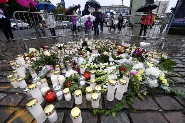 People light memorial candles at the Turku Market Square for the victims of a stabbing spree on August...