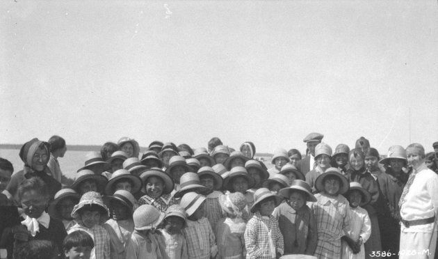 Students assemble in formal attire outside the Fort Resolution Indian Residential School in Fort Resolution,...