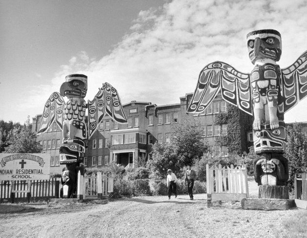 Students walk on the driveway between two totem poles at St. Michael's Indian Residential School in Alert...