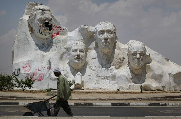 A vandalized statue of former Egyptian President Hosni Mubarak (left) dominates other sculptures of Egyptian Nobel Prize winners on a road to Cairo on May 29, 2011.