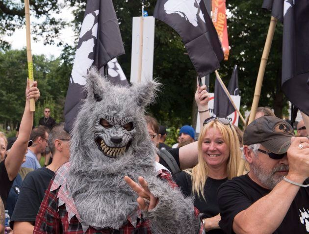 A man wearing a wolf disguise demonstrate with a right wing group,