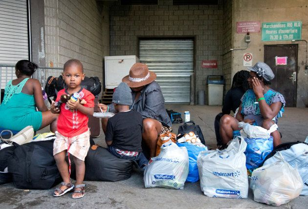 A group of Haitian asylum seekers sit with shopping bags outside the Olympic Stadium, which is being...