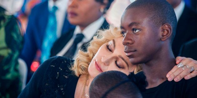 Madonna rests her head on the shoulder of her son David Banda during the opening ceremony of the Mercy...