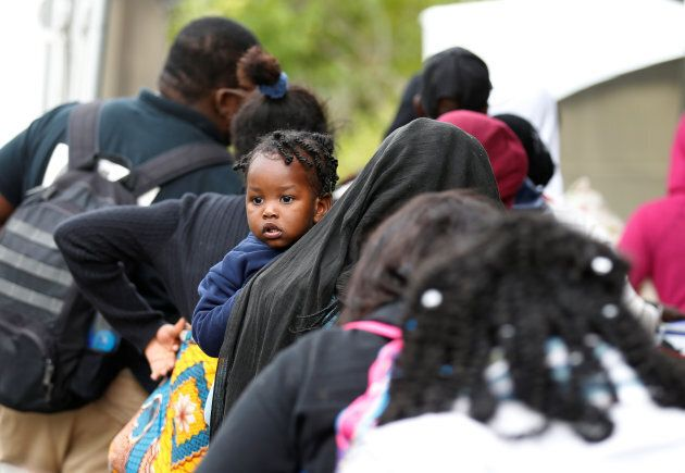 A line of asylum seekers who identified themselves as from Haiti wait to enter into Canada from Roxham Road in Champlain, New York on Aug. 7, 2017.