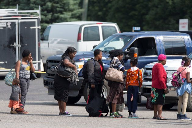 A group of asylum seekers wait to be processed after being escorted from their tent encampment to the Canada Border Services in Lacolle, Que. on Aug. 11, 2017.