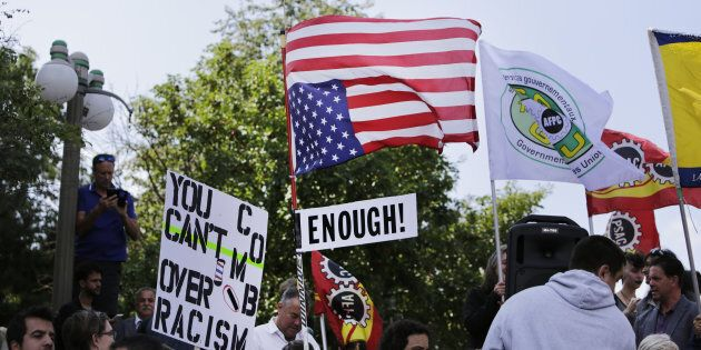 A demonstrator carries an upside-down American flag during an anti-racism rally in front of the U.S....