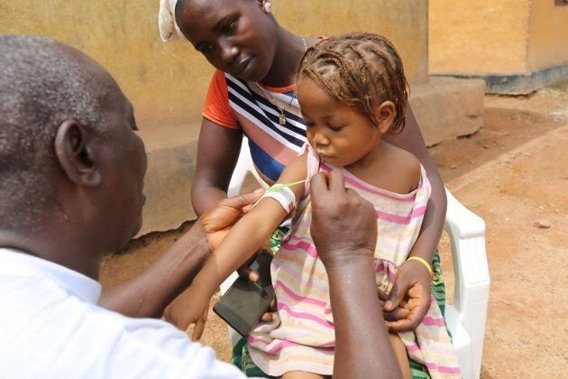 A health worker measures the arm of Hawa Kaba, 3, as her mother, Isatu Kaba, looks on.