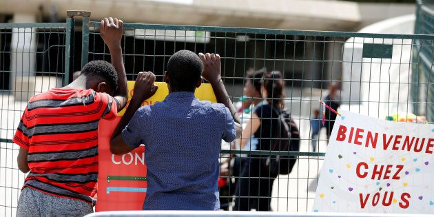 A young refugee from Angola (L) searches with a friend for his father at Olympic stadium, one of the...