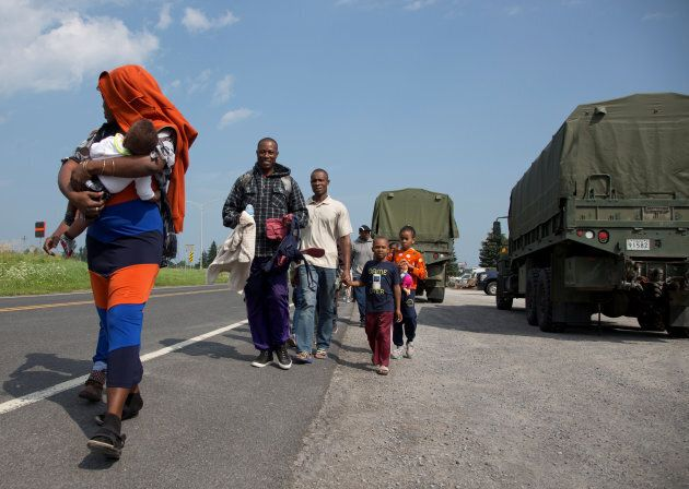 A group of asylum seekers walk down the street as they are escorted from their tent encampment to be...