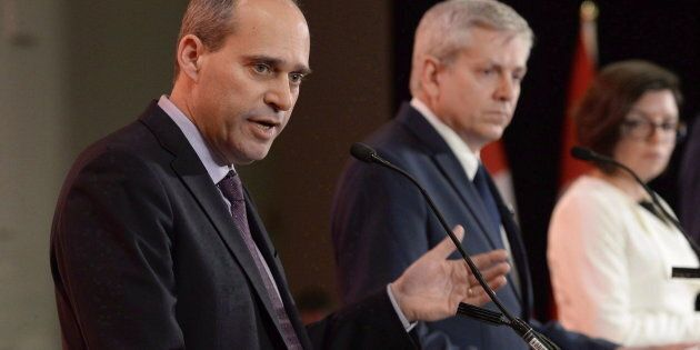 Guy Caron speaks as Charlie Angus and Niki Ashton look on in the first debate of the federal NDP leadership race in Ottawa on March 12, 2017.