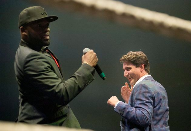 Prime Minister Justin Trudeau, right, jokes around with ring announcer Ainslie Bien-Aime during a charity...