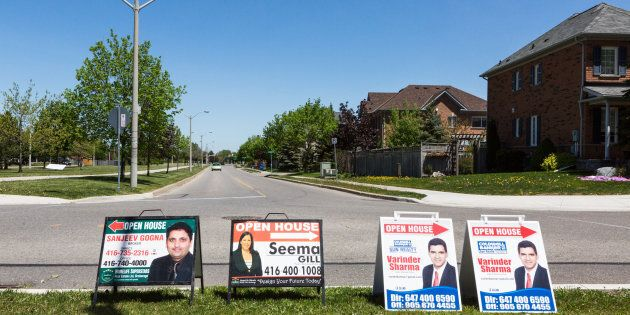 Open house signs are displayed on the side of a road in the Greater Toronto suburb of Brampton, Ontario,...
