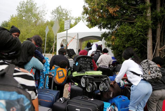 A line of asylum seekers who identified themselves as from Haiti wait to enter into Canada from Roxham Road in Champlain, New York, U.S., onAug. 7, 2017.