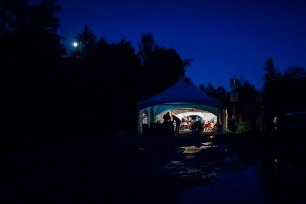 Refugees who crossed the Canada-U.S. border illegally near Hemmingford, Que. are processed in a tent after being arrested by the RCMP on Aug. 5, 2017.