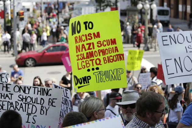 Demonstrators hold signs during an anti-racism rally in front of the U.S. Embassy in Ottawa on Aug. 23,