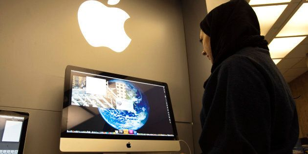 A woman uses an iMac computer in a shop at a mobile and computer shopping complex in northern Tehran...