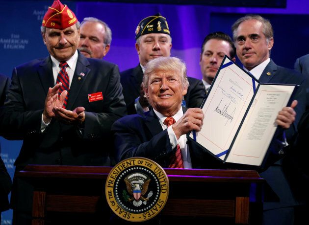 U.S. President Donald Trump holds up the Veterans Appeals Improvement and Modernization Act after signing...