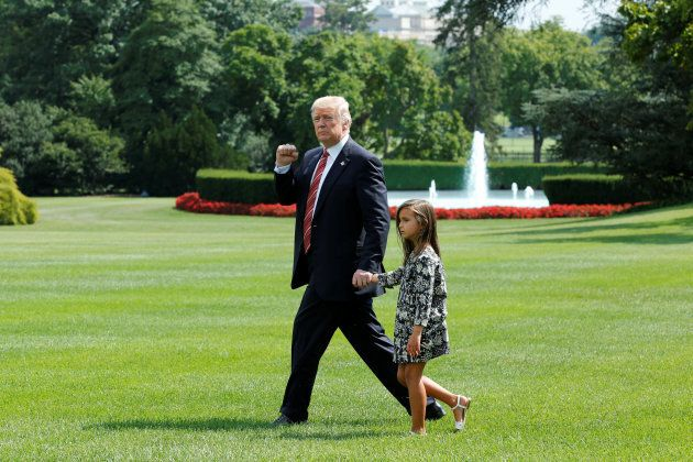 U.S. President Donald Trump gestures as he walks with his granddaughter Arabella on the South Lawn of...