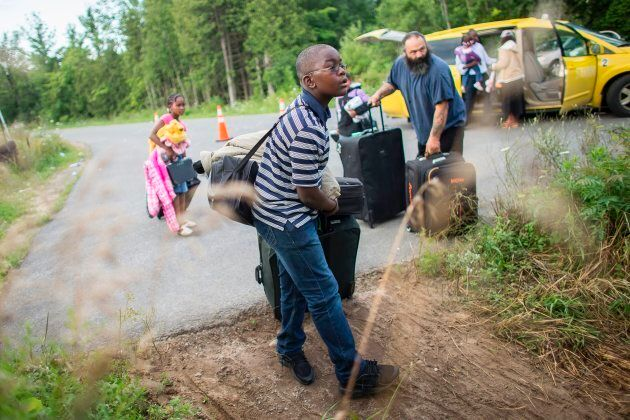 A group of people who said they were from Haiti prepare cross the border into Canada from Champlain,...