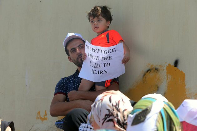 People participate in a protest to denounce plans of downsizing services to Palestinian refugees benefiting from the United Nations Relief and Works Agency (UNRWA) in front of the UNRWA schools compound at the Al-Wehdat camp, Aug. 12, 2015 in Amman, Jordan.